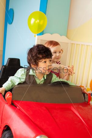 Мальчик и девочка едут в игрушечном автомобиле