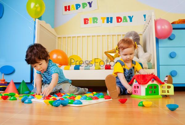 Мальчик и девочка играют с мозаикой