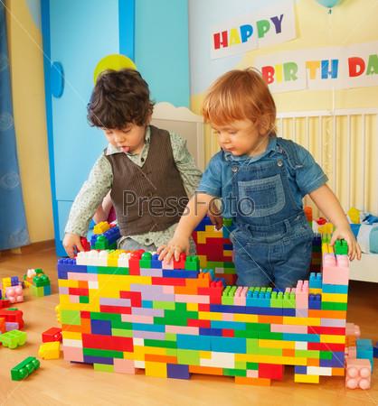Дети строят стену из пластиковых блоков
