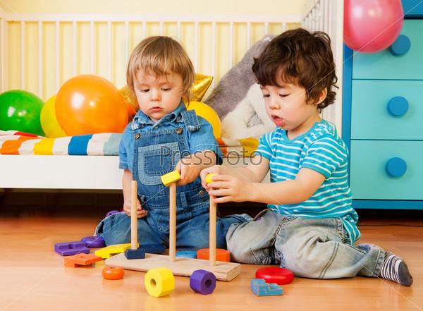 Два мальчика играют с пирамидой