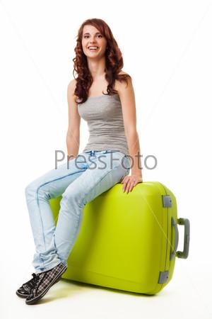 Счастливая симпатичная девушка сидит на большом зеленом чемодане