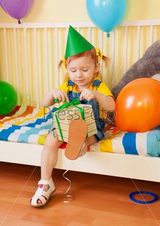 Фотография на тему Маленькая девочка открывает коробку с подарком
