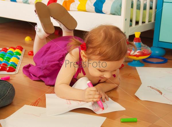 Красивая девочка рисует, лежа на полу