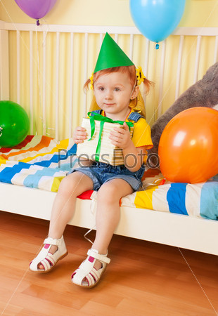 Маленькая девочка с подарком в руках в День рождения