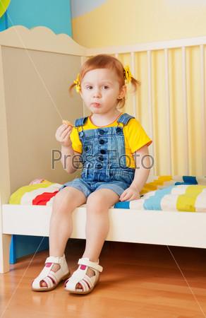 Фотография на тему Маленькая девочка кушает, сидя на кроватке
