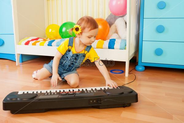 Маленькая девочка играет на синтезаторе