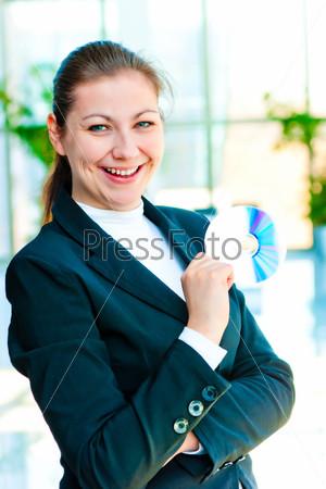 Фотография на тему Девушка в деловом костюме держит компакт-диск в руке