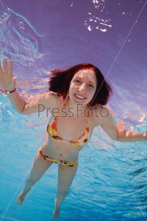 Счастливая молодая женщина плавает под водой