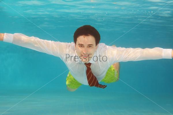 Деловой человек плавает под водой в бассейне