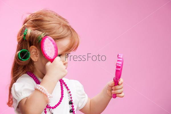 Маленькая девочка играет в парикмахера