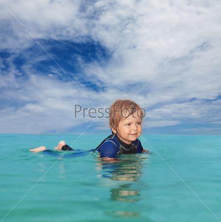 Маленький мальчик лежит в воде