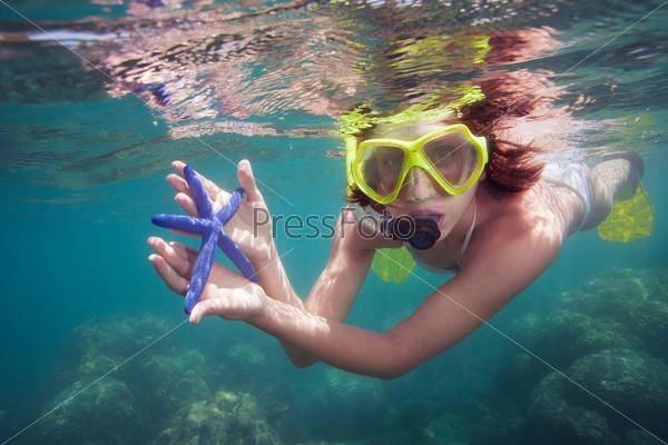 Девушка держит морскую звезду