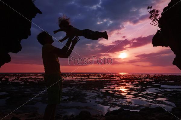 Фотография на тему Отец подбрасывает своего ребенка вверх