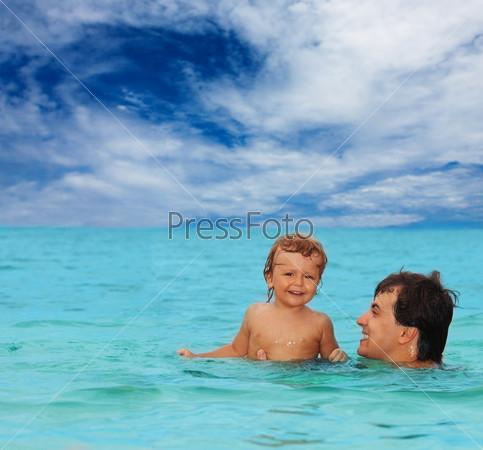 Фотография на тему Папа с сыном плавают вместе в море