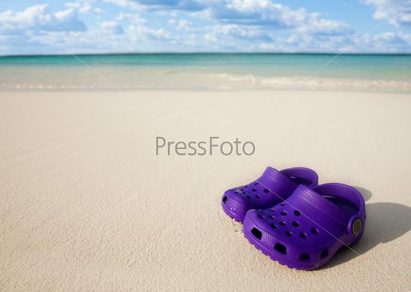 Фотография на тему Маленькие детские ботинки на песчаном пляже