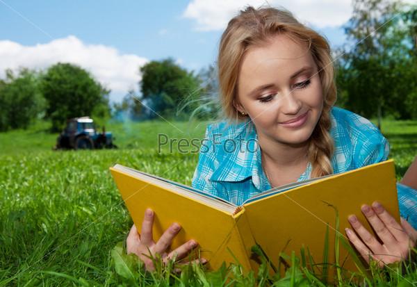 Красивая девушка читает книгу на открытом воздухе
