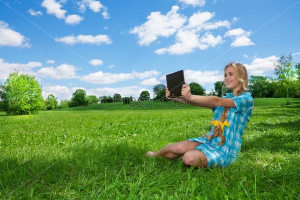 Девушка на лужайке с планшетным компьютером