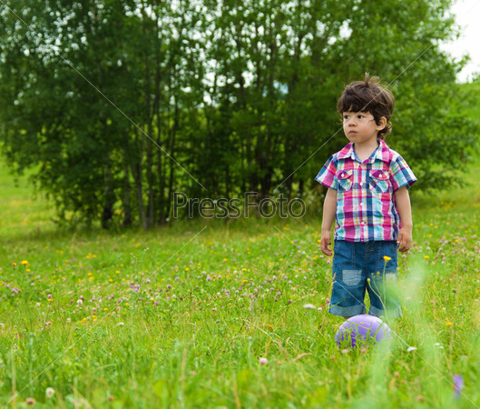 Маленький мальчик с мячом в траве
