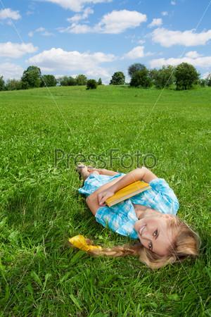 Улыбающаяся девушка, лежащая на лужайке