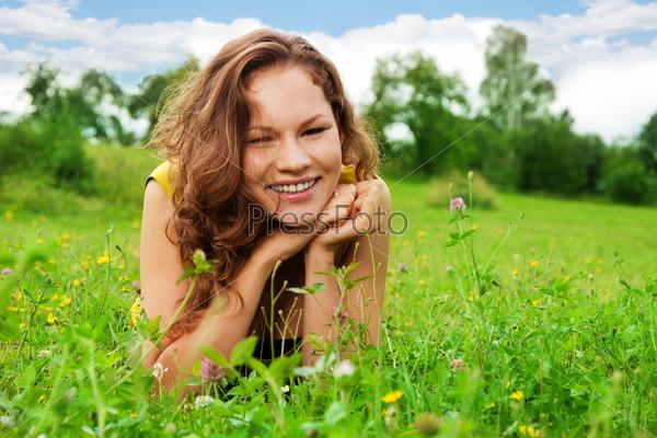 Симпатичная девушка, лежащая на зеленой траве