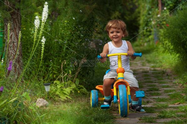 Мальчик едет на трехколесном велосипеде