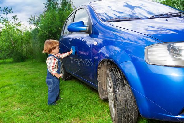 Очаровательный ребенок помогает мыть автомобиль