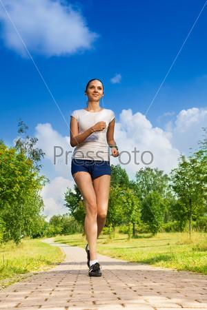 Стройная высокая девушка бегает в парке