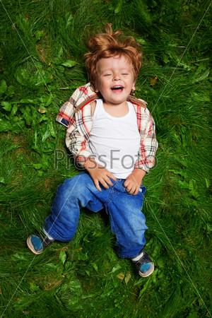 Очаровательный ребенок смеется на траве