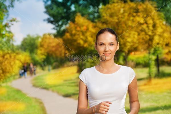 Симпатичная уверенная женщина бегает трусцой