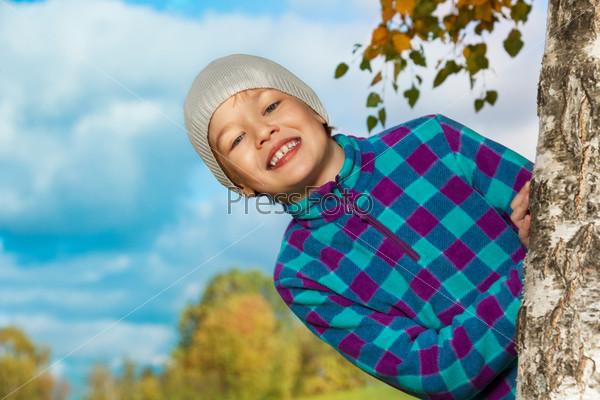 Фотография на тему Счастливый ребенок выпрыгнул из-за дерева