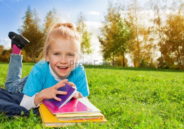 Милая маленькая девочка с книгами в парке