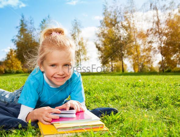 Мило улыбающаяся белокурая девочка в парке
