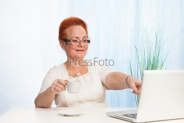 Пожилая женщина показывает на экран ноутбука