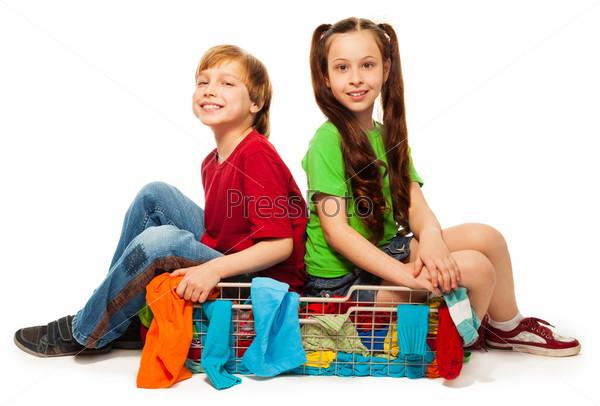 Двое детей в корзине с одеждой