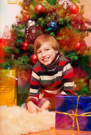 Милый счастливый мальчик ждет открытия подарков