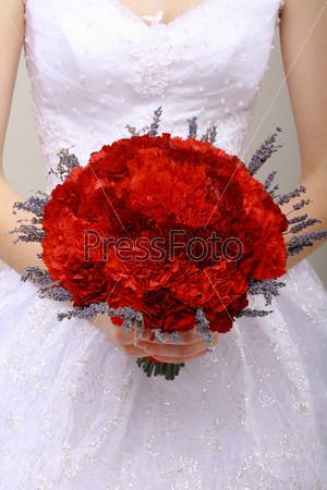 Букет из красных цветов в руках невесты