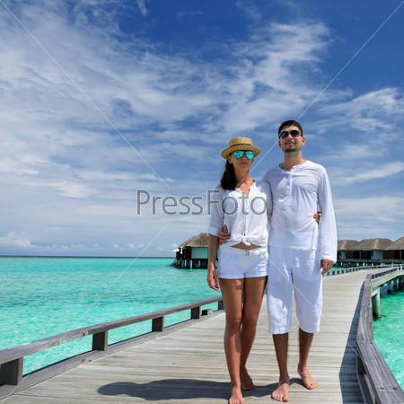 Молодая пара на пристани в Мальдивах