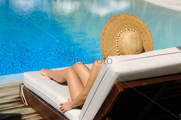 Женщина отдыхает возле бассейна