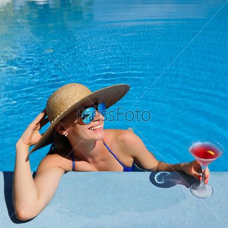 Женщина у бассейна с коктейлем