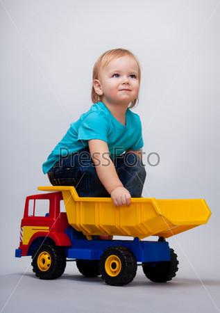 Малыш сидит на игрушечном грузовике