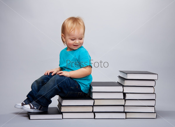 Ребенком сидит на лестнице из книг