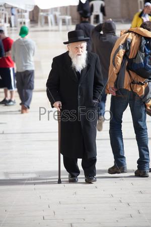 Старый ортодоксальный еврей с тростью возле Западной стены