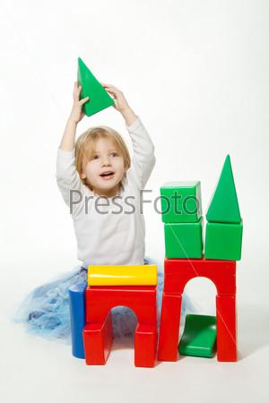 Маленькая девочка строит дом из кубиков