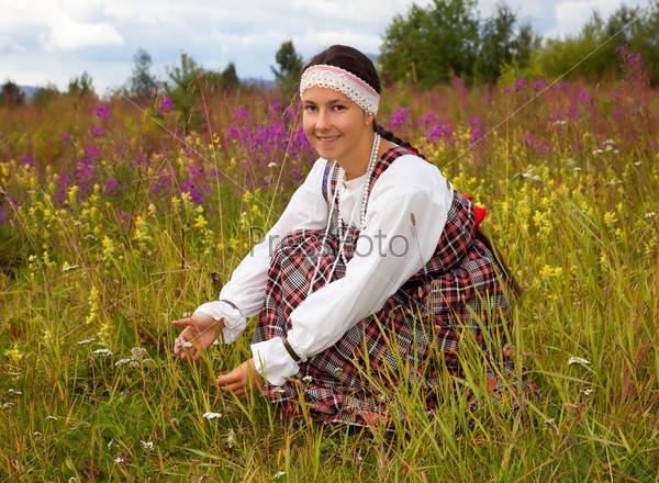 Молодая красивая девушка собирает полевые цветы