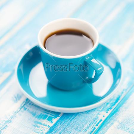 Чашка черного кофе на деревянных досках, крупный план