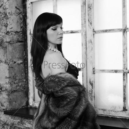 Чувственная брюнетка в шубе у окна, черно-белый портрет