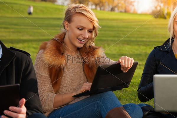 Светловолосая студентка с ноутбуком смеется