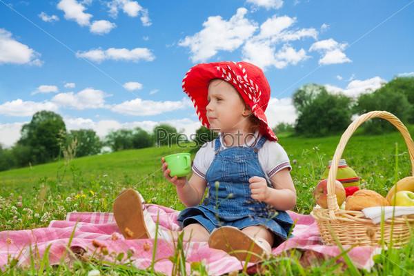 Маленькая девочка пьет на пикнике