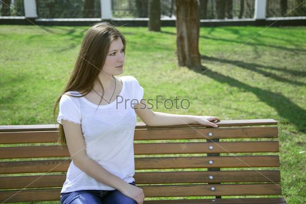 Фотография на тему Молодая красивая женщина одна на скамье в парке