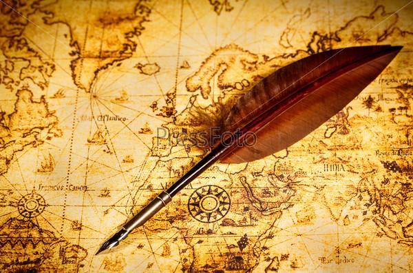 Винтажное гусиное перо лежит на старой карте